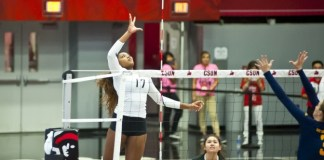 A CSUN student, (number 17) spike the volleyball over net over the heads of the team's opponents.