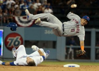 A Dodger player falls onto the ground as his opponent (New York 11) jumps over him to throw the ball.