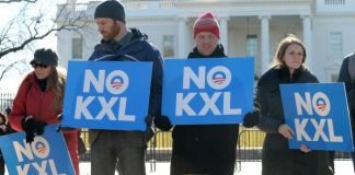 """Protestors stand outside of the White House holding signs that read """"No KXL"""""""