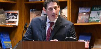 Brian Levin stands behind podium