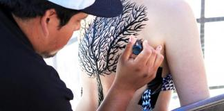 Artist draws tree on girls entire back