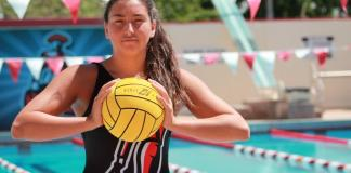 Water polo athlete poses with ball outside of pool
