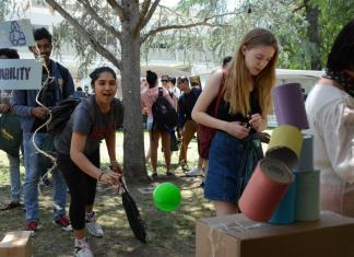 Student knocks over cans by throwing a ball