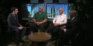 Three men sit along one another while being interviewed by another man