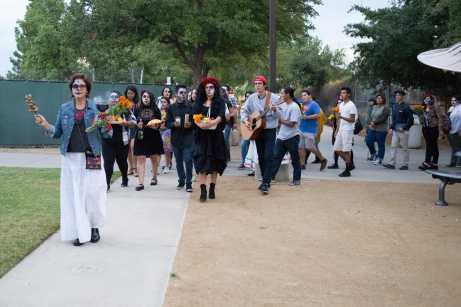 People march carrying offerings for deceased family at CSUN