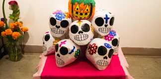 Photo shows an altar displaying handmade skulls and a paper jackolantern