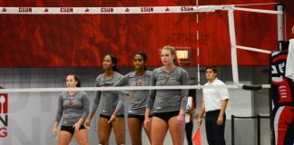 CSUN volleyball team stands in formation before the game begins again