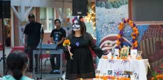 Woman shown in skull makeup in front of a Dia de los muertos altar