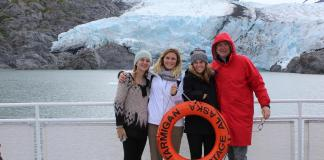 4 people pictured standing on a boat next to a glacier in Alaska