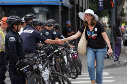 """Woman, whose shirt reads, """"Love trumps hate"""", shakes hands with police officers"""