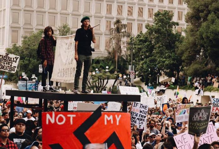 A large mob of protesters stand together holding posters and banners