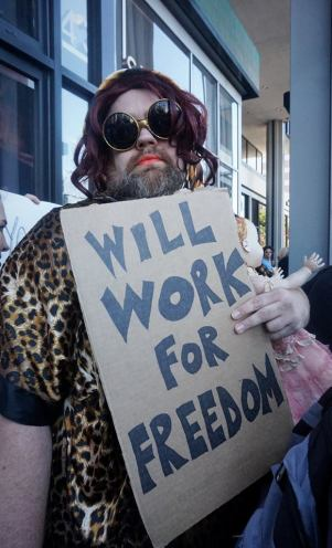 """Man dressed in drag holds sign that reads, """"will work for freedom"""""""