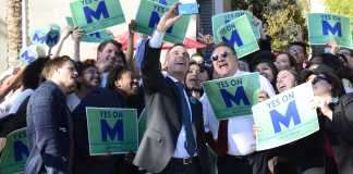 "Mayor shown taking picture with people holding signs that read, ""Yes on M"""