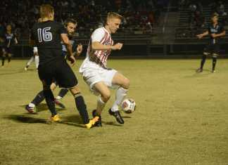 CSUN soccer player runs to take the ball from opposing team