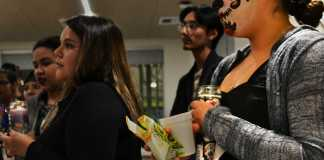 CSUN students gather for Day of the Dead celebration holding candles and donning skull makeup