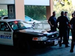 Police officers gather around student in parking garage