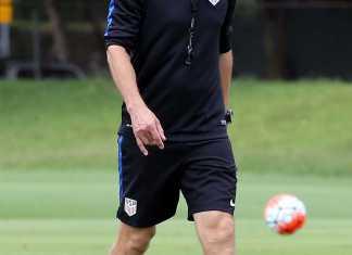 Soccer coach walks across field