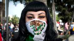 Protester is shown with a Mexican flag wrapped around her nose and mouth