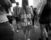 """Several protesters shown from the back, one girl has a shirt which reads, """"Silence is violence"""""""
