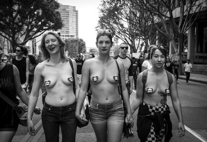 Three female protesters are shown wearing pasties in the shape of hearts with equality symbols