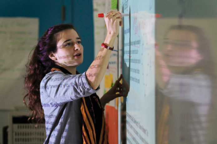 Woman is shown writing on a white board