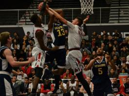 CSUN basketball players jump up to block opposing team's shot