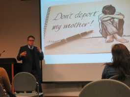 """Man gives a presentation with an image that shows a boy crying with text that reads, """"don't deport my mother"""""""