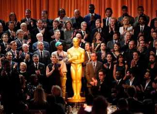 ACademy Awards nominees are all gathered around a giant oscar