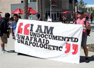 "Students hold up poster that says, ""I am undocumented unafraid unapologetic"""