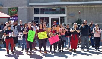 Students holding signs and circled around chanting several phrases during the protest about their concerns with the invitation of U.S. Customs and Boarder Patrol to the career fair. (Photo credit: Alejandro Aranda)