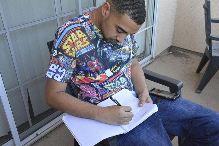 Brandon Hudson pictured writing in his notebook
