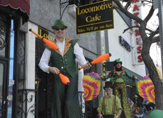 people on stilts walk past the locomotive cafe