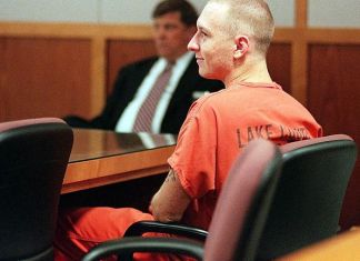 Rod Ferrell sits in court looking content wearing an orange jumsuit