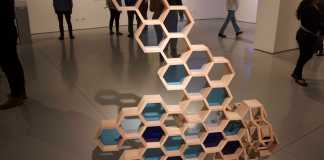 art piece shows connected hexagons with stained glass in the center