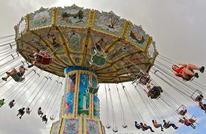 people pictured riding a large circular swing at the fair