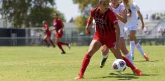 csun soccer player looks focused as she blcoks the other team's player
