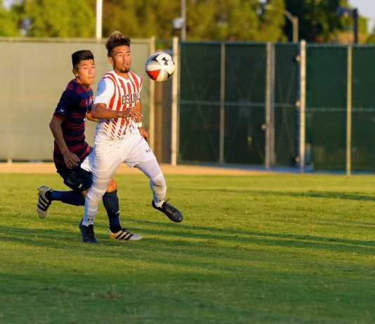 CSUN player runs for the ball while blocking another player