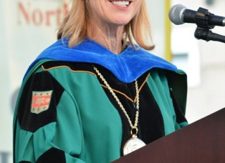 president Dianne F. Harrison wearing traditional teal blue and black graduation garment