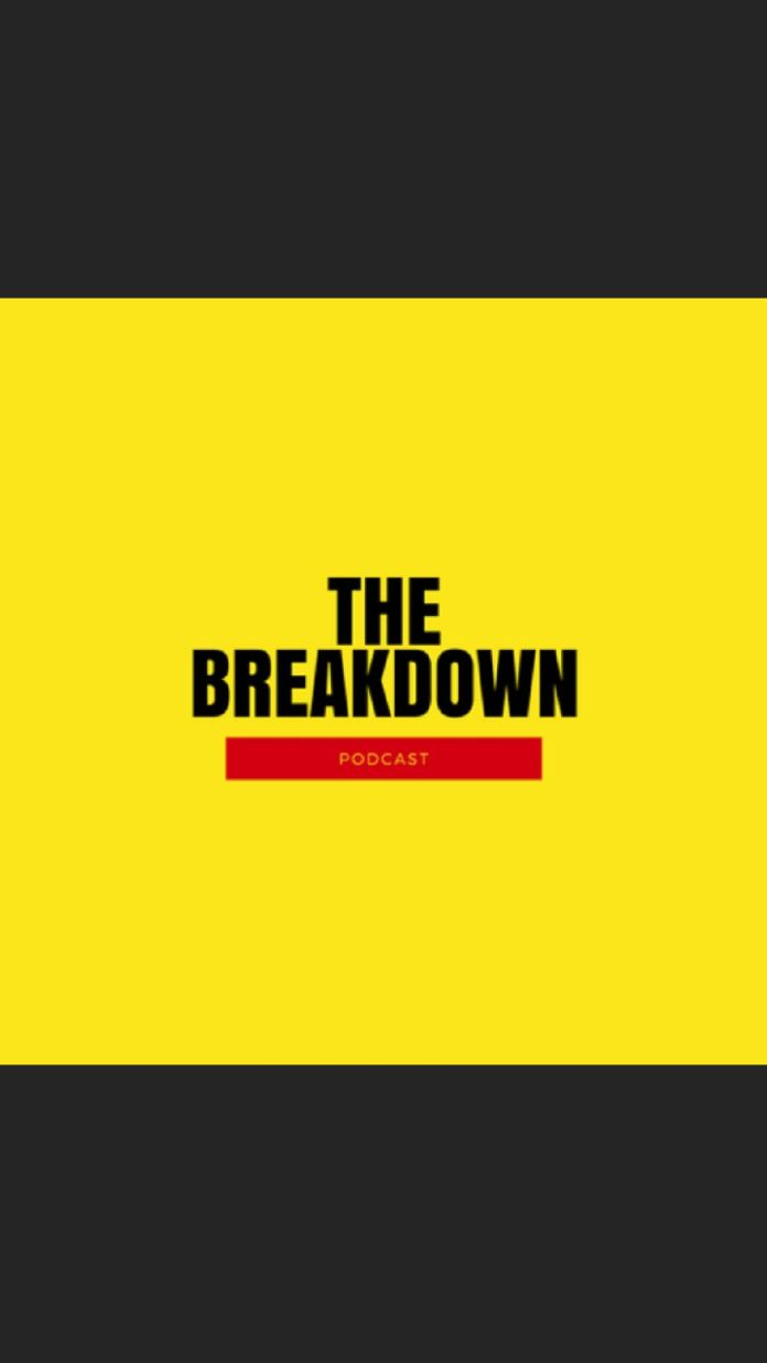 yellow sign with black lettering saying The Breakdown with a red bar that has Podcast written inside