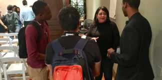three male students speaking to woman in a circle