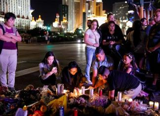 crowd on Las Vegas strip in front of candles and flowers on the floor