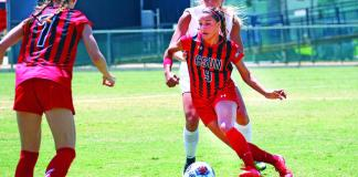 csun womens soccer players in red and black playing soccer