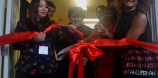 red ribbon being cut by large red scissors