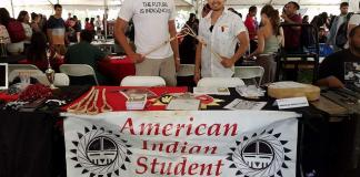 two male students stand behind American Indian Student Association booth