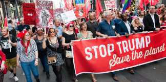 protestors march with large red sign reading STOP TRUMP SAVE THE PLANET