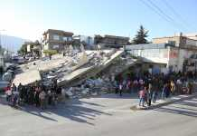 people stand around collapsed building