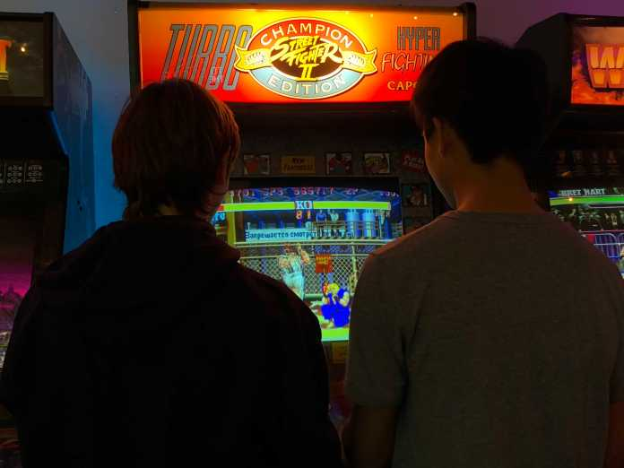 two students play an arcade game