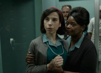 woman in blue shirt and grey cardigan being held by woman in blue collard shirt and brown cardigan