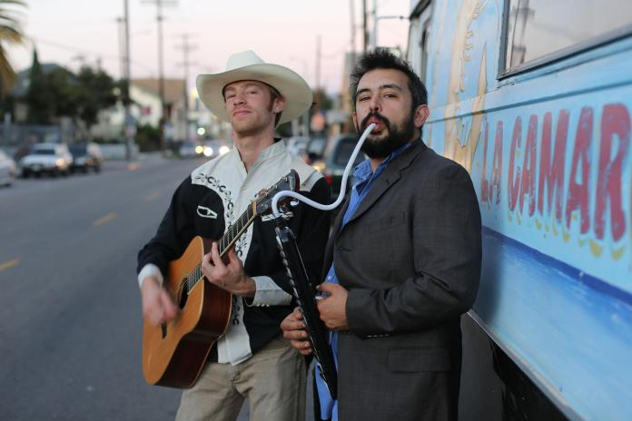 man holding guitar and man holding keyboard