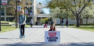 student sits in protest with red tape over her mouth